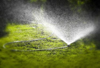 Watering the lawn of a private house with the help of irrigation sprinkler.